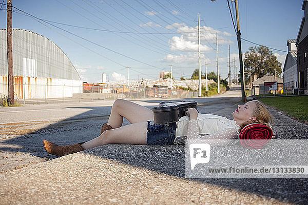 Nachdenkliche Frau liegt auf Bürgersteig gegen Strommasten