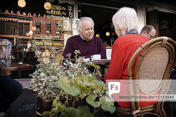 Älteres Ehepaar unterhält sich im Straßencafé