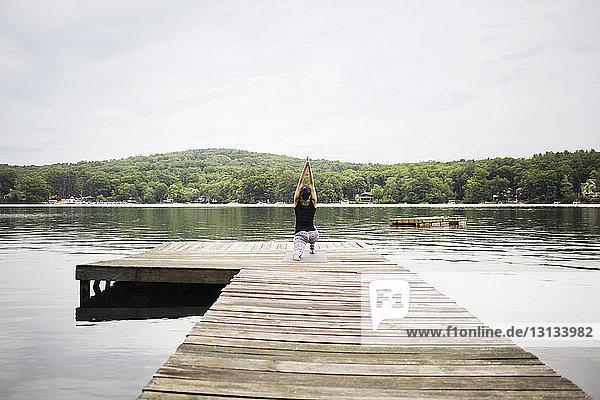 Rückansicht einer Frau  die auf einem Pier am See gegen den Himmel trainiert