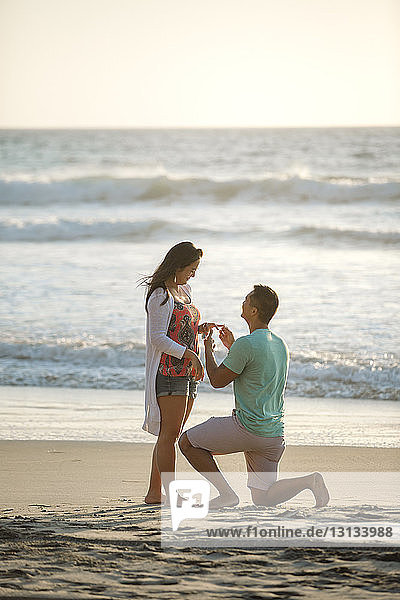 Boyfriend proposing marriage to girlfriend while kneeling at beach against sea and sky