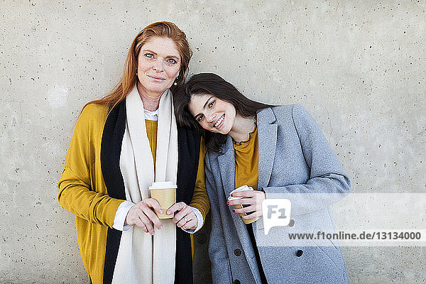 Portrait of daughter and mother with disposable cup standing against wall in city