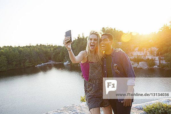 Cheerful friends taking selfie through camera by lake during sunset