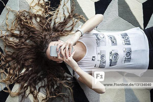 Draufsicht einer Frau  die ein Smartphone benutzt  während sie zu Hause auf dem Teppich liegt