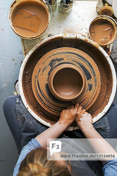 Overhead view of woman working on pottery wheel
