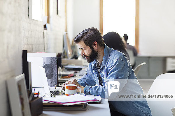 Seriöser Geschäftsmann mit Laptop am Schreibtisch im Kreativbüro