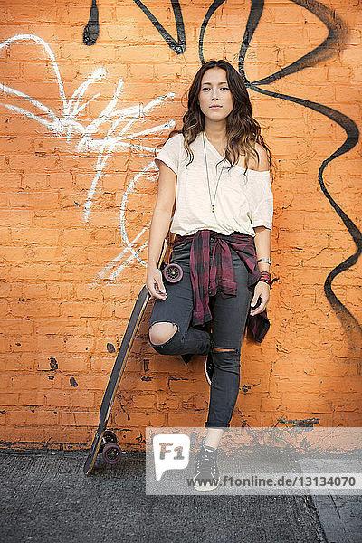Porträt einer jungen Frau mit Skateboard an einer Ziegelmauer lehnend