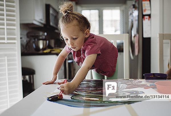 Mädchen malt auf Papier  während sie zu Hause am Tisch steht