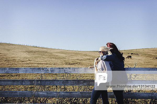 Mutter und Tochter stehen am Zaun am Feld gegen den klaren Himmel