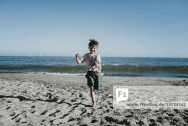 Carefree boy running at beach against clear sky during sunny day