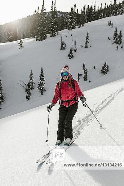 Frau fährt Ski auf schneebedecktem Berg im Wald
