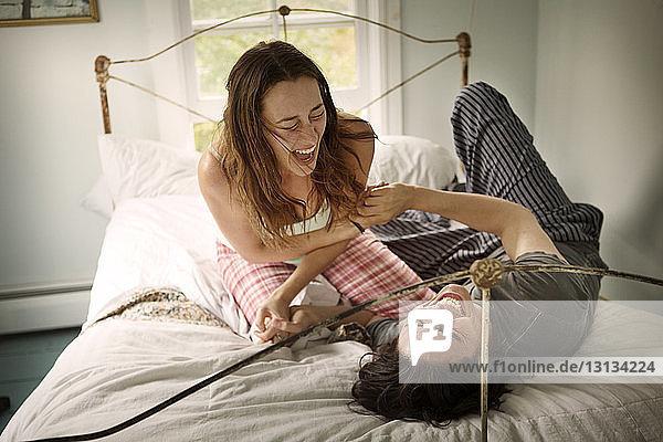 Lachendes Paar beim Spielen auf dem Bett im Schlafzimmer