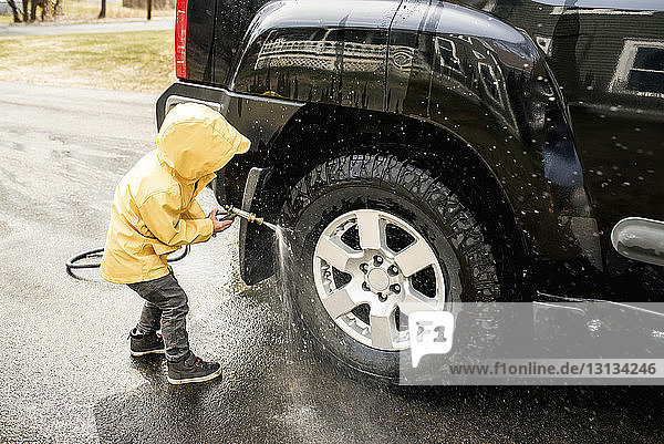 Boy cleaning sports utility vehicle on road