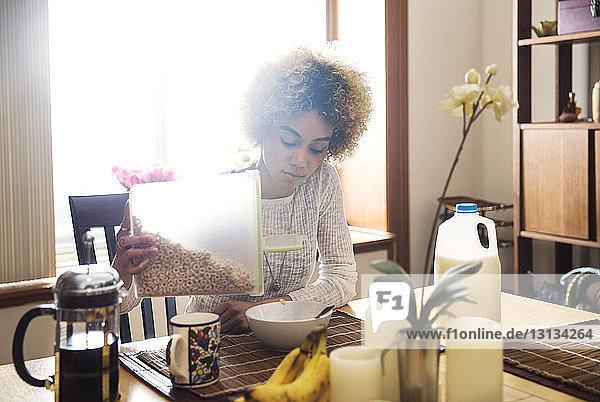 Junge Frau schüttet bei Tisch im Haus Getreide in Schüssel