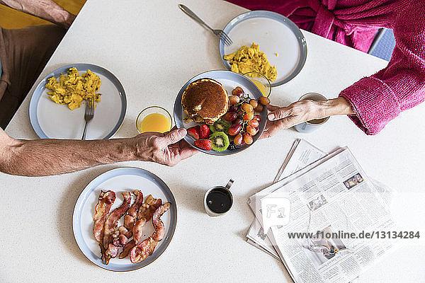 Mittelteil eines Paares  das einen Teller mit Essen über dem Esstisch zu Hause hält