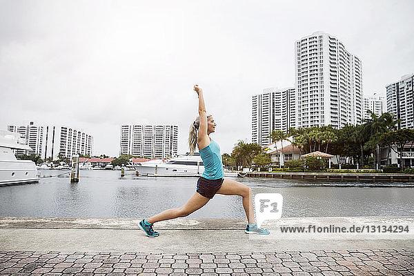 Seitenansicht einer reifen Frau  die in Krieger-I-Pose auf dem Fußweg Yoga praktiziert