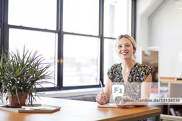 Porträt einer lächelnden Geschäftsfrau mit Mobiltelefon  die im Büro am Tisch sitzt