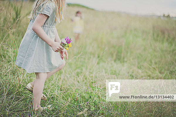 Side view of girl holding flowers on field with sister in background