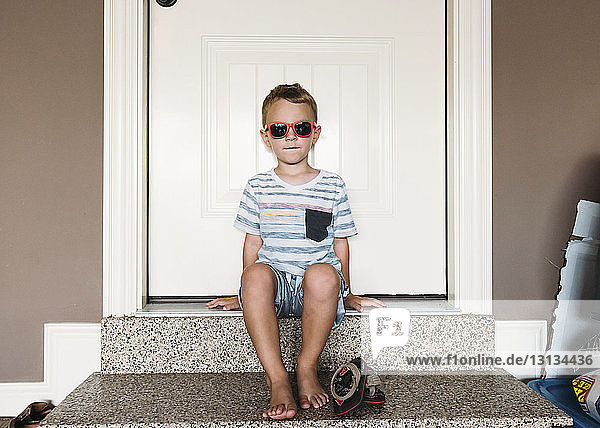 Full length of boy wearing sunglasses sitting on doorway