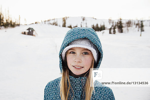 Portrait of girl standing on snow covered field