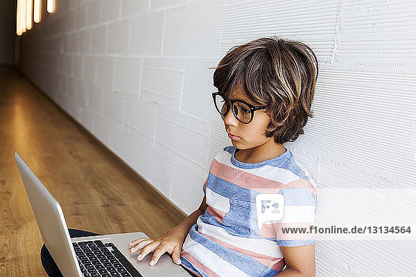 Boy using laptop computer while sitting on hardwood floor by wall at home