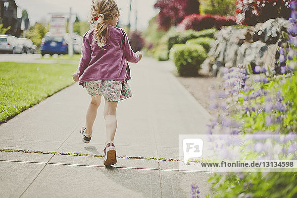 Rear view of girl walking on footpath