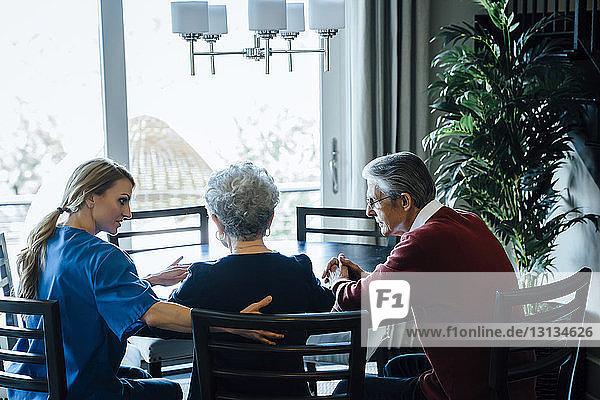 Hausangestellte diskutiert mit älterem Paar am Esstisch