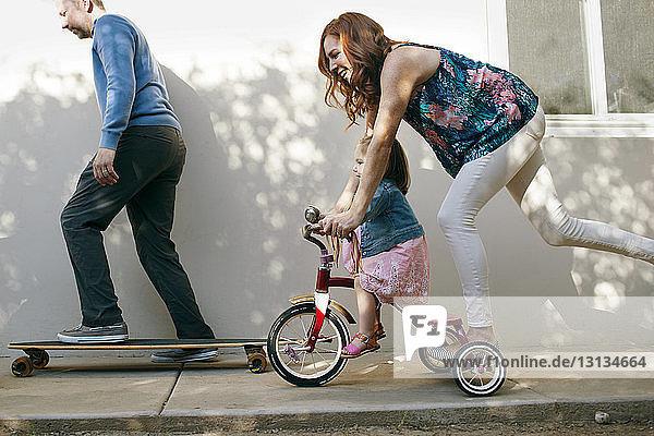 Mädchen fährt Dreirad mit der Mutter  während der Vater im Garten Skateboard fährt