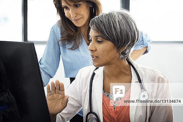 Ärztin erklärt Patienten in der Klinik den Bericht am Computer