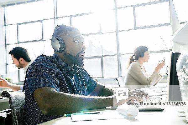 Geschäftsmann benutzt Desktop-Computer bei der Arbeit mit Kollegen im Büro