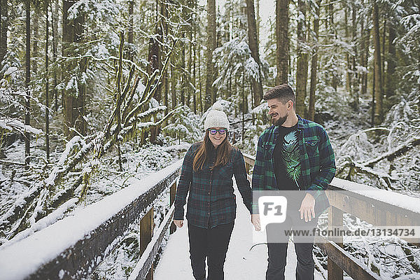 Couple holding hands while walking in forest at Lynn Canyon Park during winter
