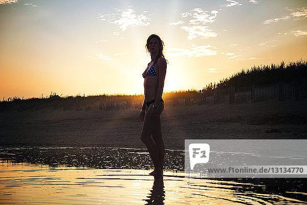 Woman wearing bikini standing at beach against field during sunset