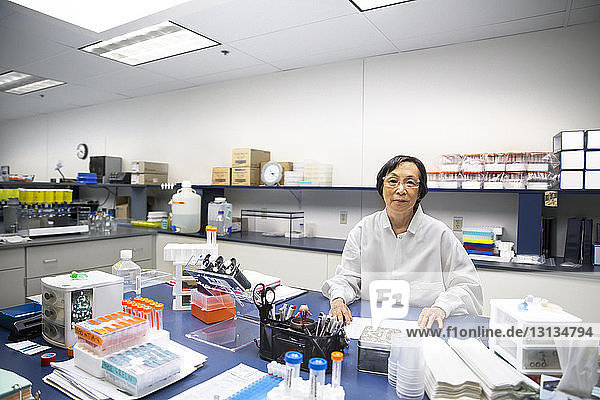Portrait of confident senior female scientist in laboratory