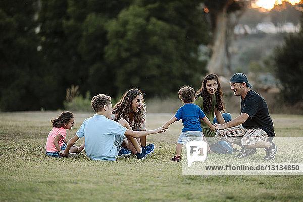 Fröhliche Familie spielt im Park Ringelreihen um den Rosenkranz