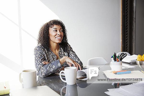 Lächelnde Geschäftsfrau sitzt am Tisch und schaut im Büro weg