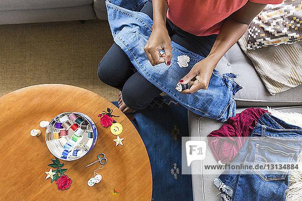 Schrägansicht einer Frau  die den Faden von der Spule entfernt  während sie zu Hause auf dem Sofa sitzt
