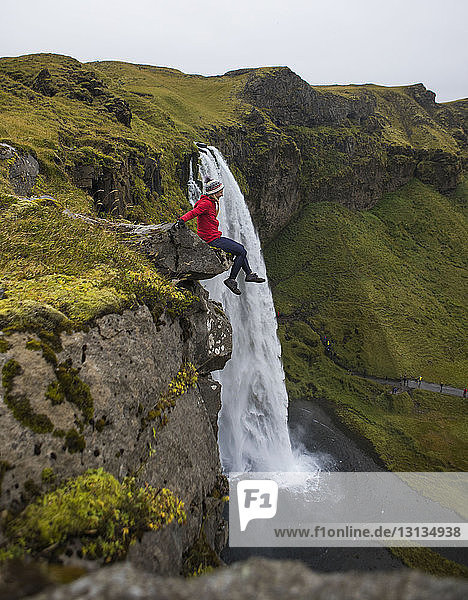 Seitenansicht eines Wanderers  der auf einem Felsen vor einem Wasserfall sitzt