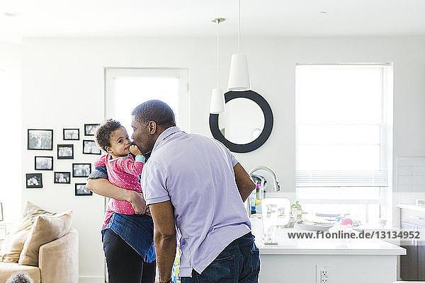 Mann küsst Baby  das von Frau zu Hause getragen wird