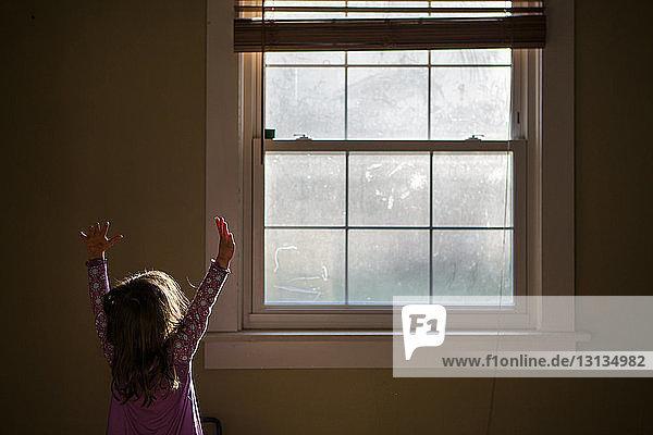Mädchen mit erhobenen Armen steht zu Hause am Fenster