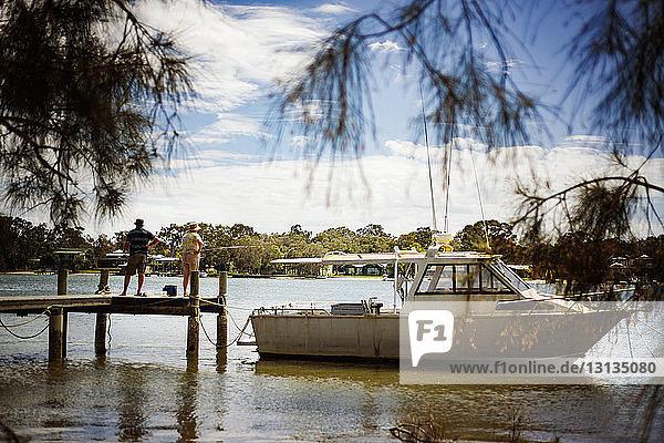 Rückansicht eines älteren Mannes und einer älteren Frau  die mit einem auf dem See vertäuten Boot am Pier stehen