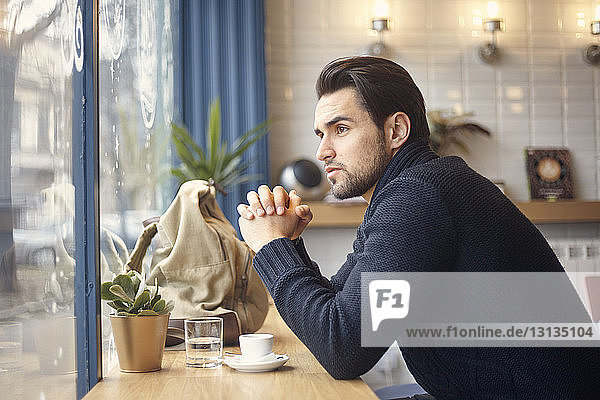 Side view of thoughtful man looking through window while sitting at cafe
