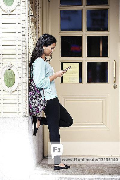 Seitenansicht einer Frau  die einen Tablet-Computer benutzt  während sie an der Tür steht