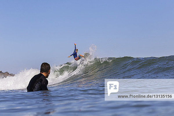 Man looking at friend surfing on sea against clear blue sky