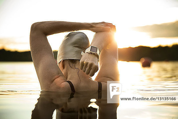Rear view of female swimmer stretching arms in lake during sunset