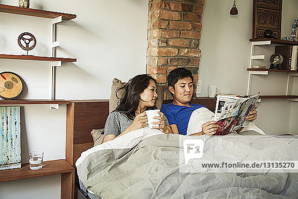 Husband and wife reading magazine while relaxing on bed at home