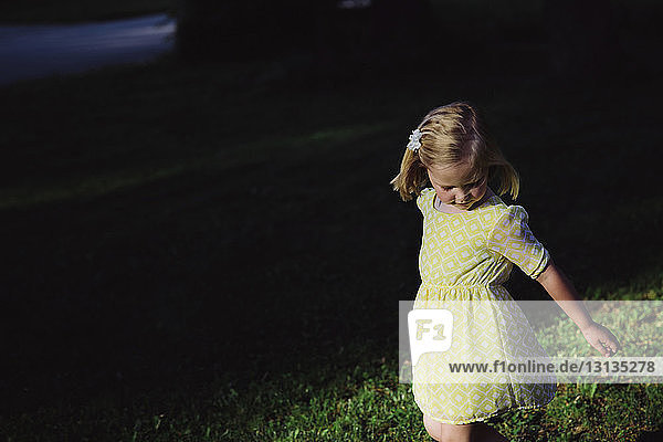 High angle view of girl standing on grassy field at park