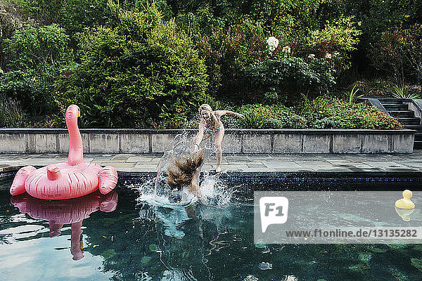 Verspieltes Teenager-Mädchen schubst Freundin ins Schwimmbad