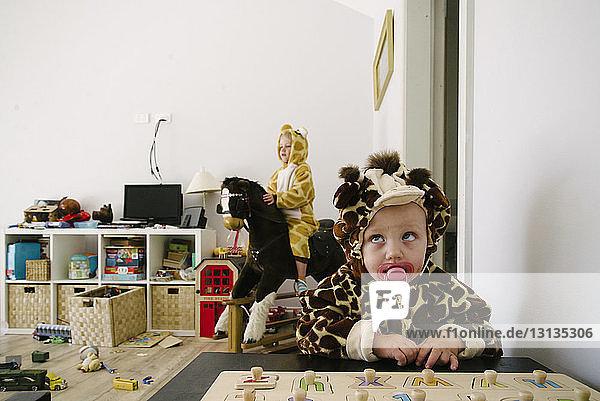 Zu Hause spielende Geschwister in Tierkostümen