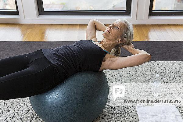 Ältere Frau mit Händen hinter dem Kopf auf dem Fitnessball liegend  während sie zu Hause Sport treibt