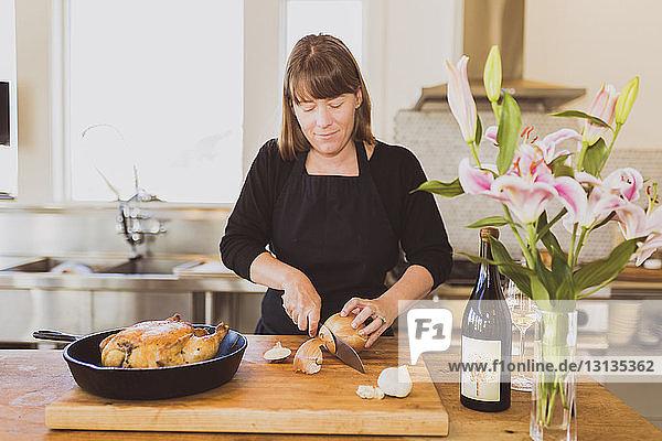 Frau schneidet Zwiebel auf Schneidebrett bei Tisch