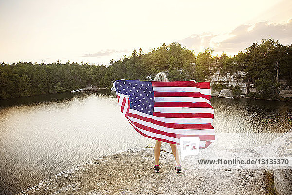 Rear view of woman holding American flag on rock overlooking lake